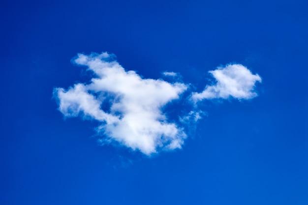 青い空を背景に孤独な白いふわふわの雲
