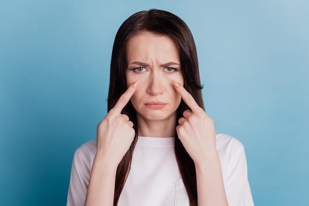 Одинокая женщина плачет, указывая пальцами слезы, изолированные на синем фоне