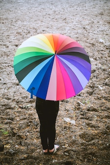 Lonely woman holding umbrella standing on dry ground