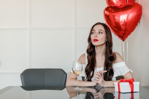 Lonely woman at home with present and heart shaped balloons drinking wine