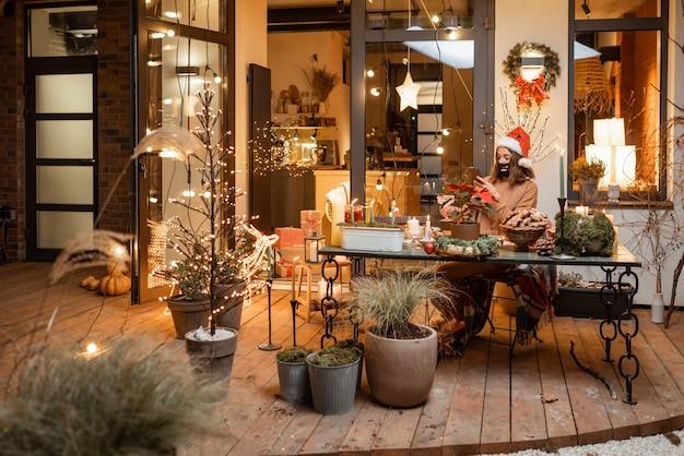Одинокая женщина в маске для лица во время новогодних праздников дома на красиво оформленной террасе. концепция карантина и самоизоляции во время эпидемии в праздничные дни
