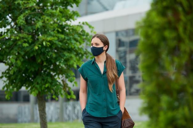 의료 얼굴 마스크에 외로운 여자 바지 주머니에 손을 밀어 나무 사이 산책