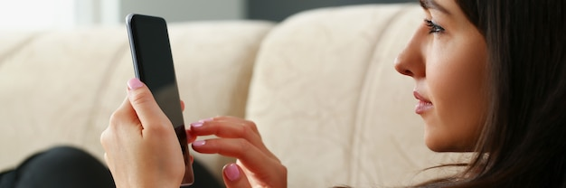 Lonely woman is sitting on couch and looking into smartphone. social networks and loneliness in the modern world concept
