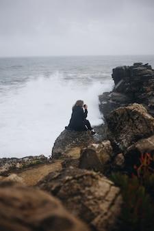 La donna sola si siede sulla scogliera nella tempesta di pioggia