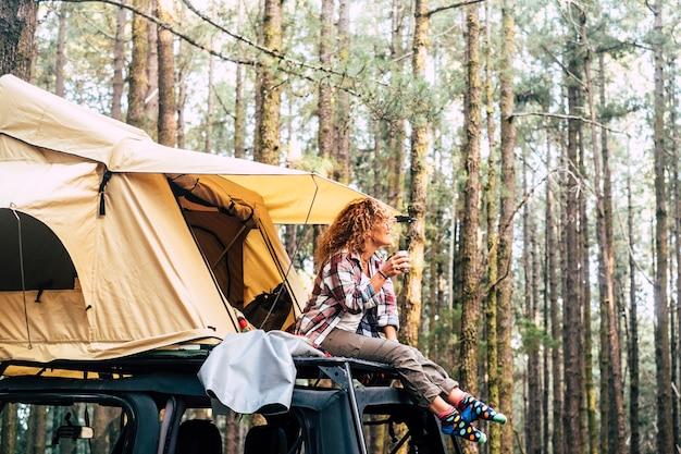 孤独な女性がルーフテントの外の車の屋根に座る