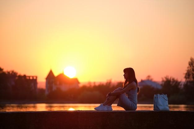 Одинокая женщина, сидящая одна на берегу озера в теплый вечер. уединение и расслабляющий отдых на природе.