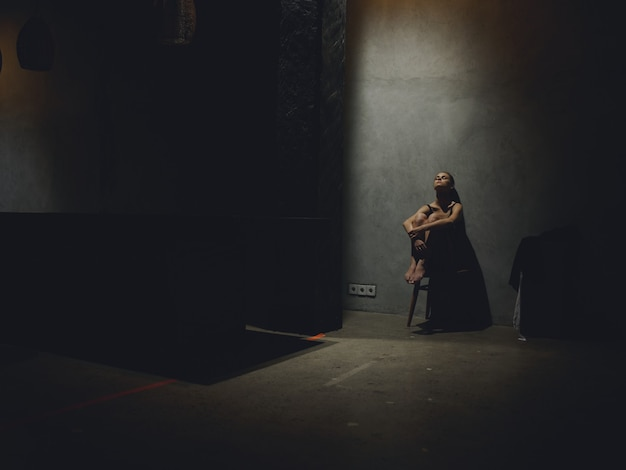 壁にもたれて暗い部屋で椅子に座っている孤独な女性
