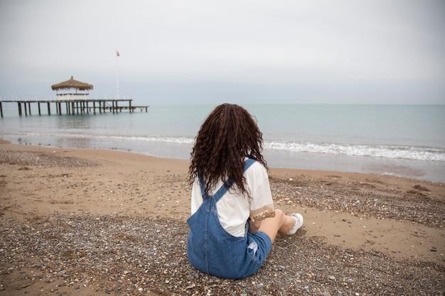 ビーチに座っている孤独な女性