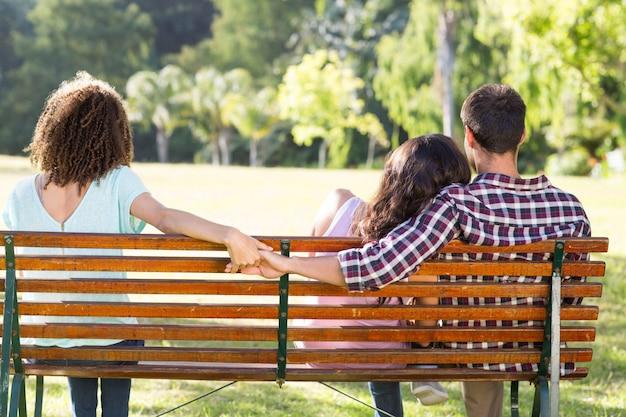 Одинокая женщина, сидящая с парой в парке