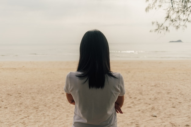 Lonely woman stand on the beach and look into the sea.