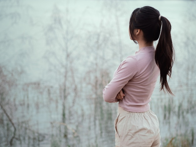 Lonely woman standing alone beside the river. lonely, sadness concept.