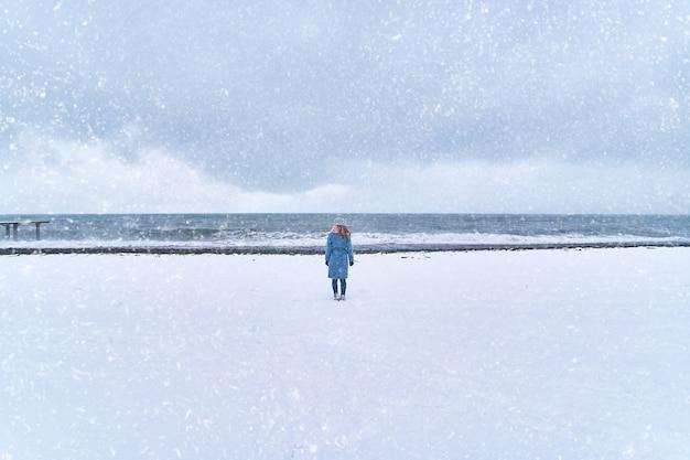 Одинокая женщина стоит в метель на снежном берегу