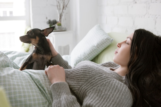 Lonely woman wake up with dog. friendship with small puppy, single girl morning with pet
