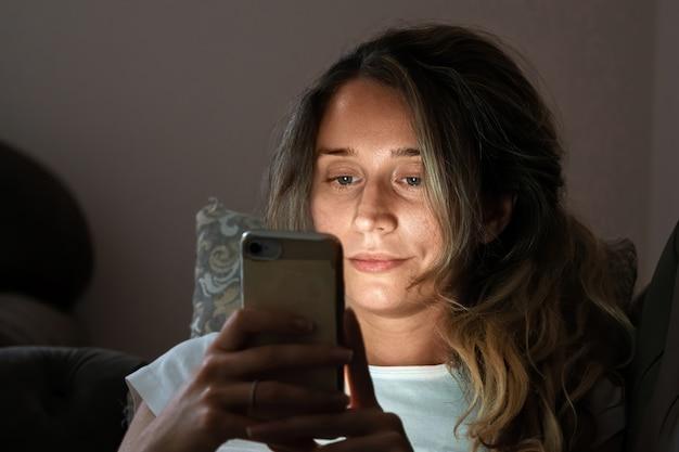 夜のベッドで携帯電話を見ている孤独な女性