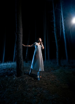 Lonely woman in white nightgown looking at beam of light at night forest
