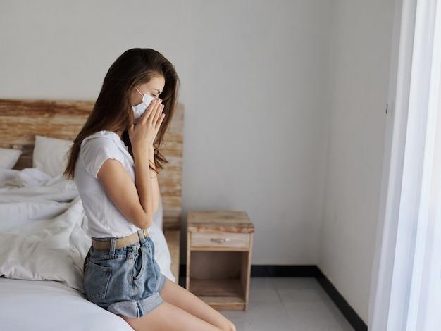 彼女の顔に医療マスクを持つ孤独な女性はベッドに座っています