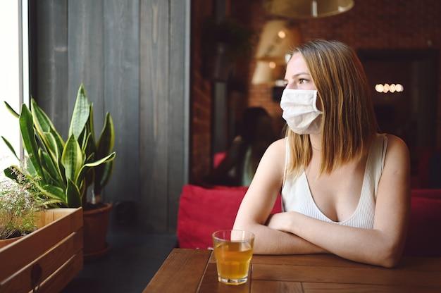 Одинокая женщина с защитной маской в кафе