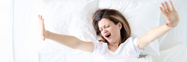 Lonely woman yawns and stretches in bed rest and relaxation after working day concept