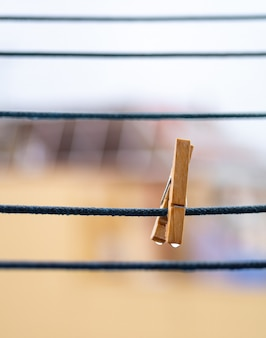 Lonely wooden clothespin on a blue ropes with hanging drops