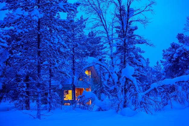 외로운 나무 오두막은 겨울 숲의 저녁 덤불에서 빛납니다. 많은 눈