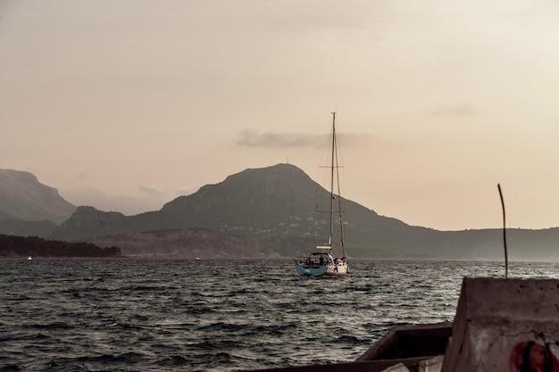 Одинокая яхта плывет из порта вечером