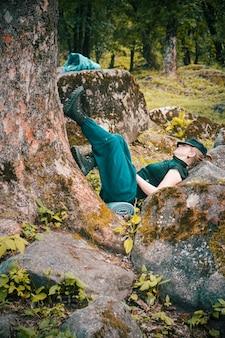 나무와 암석 옆에서 자고 있는 외로운 젊은 여성