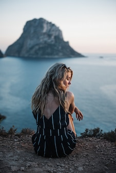 그녀의 평화로운 시간을 즐기고 바다에 앉아 금발 머리를 가진 외로운 젊은 여성