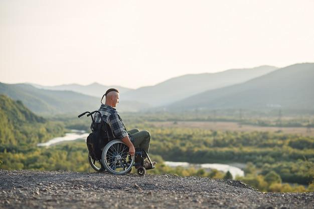 山の晴れた日に新鮮な空気を楽しんでいる車椅子の孤独な青年