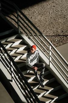 眼鏡をかけた孤独な若い男は、都市の建物やビューの上の都市空間のコンクリートの階段に一人で座っています