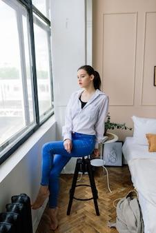 自宅で白いシャツを着た孤独な若い女性