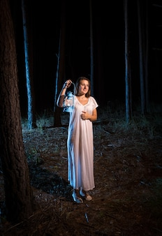 Lonely young woman in nightgown walking in forest at night with gas lamp