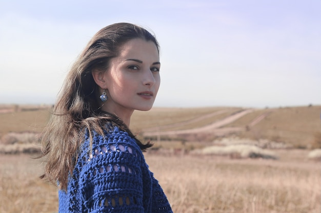외로운 젊은 여자 초상화입니다. 바람에 날리는 긴 머리.