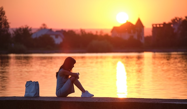 Lonely young woman sitting alone on lake shore enjoying warm evening. wellbeing and relaxing in nature concept.