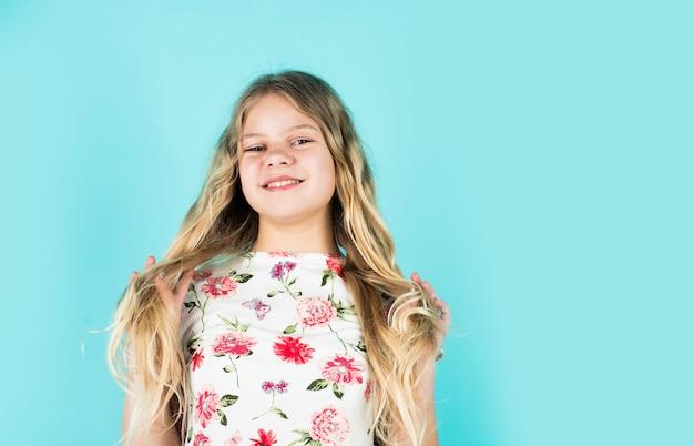 長くて健康な髪。ファッションと美容。美容院の小さな女の子。小さな幸せな子供は非常に巻き毛のブロンドの髪をしています。子供のための髪型。美しくトレンディに見えます。コピースペース。