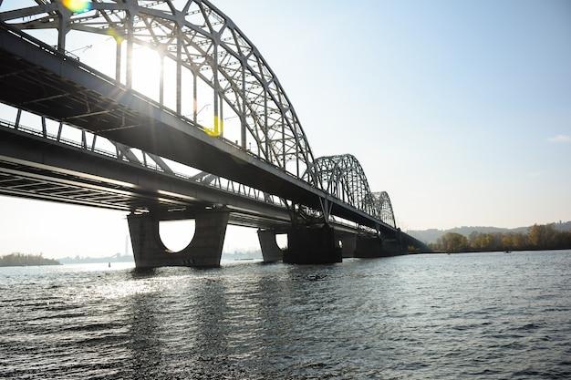 広い川に架かる長いアーチ型の鉄橋。太陽光線が通り抜けます。