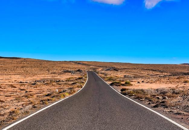 スペイン、カナリア諸島のブッシュフィールドの長いアスファルト道路