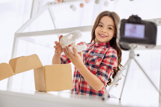 Long-awaited gift. joyful pre-teen girl in a checked shirt holding a model of the dinosaur skull and showing it to the camera, having opened the parcel