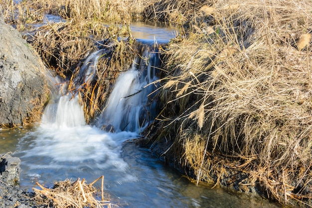 Long-awaited spring creeks flow over ravines and hills on a sunny day. water rapids and waterfalls of streams among the dry grass. beautiful spring landscape.