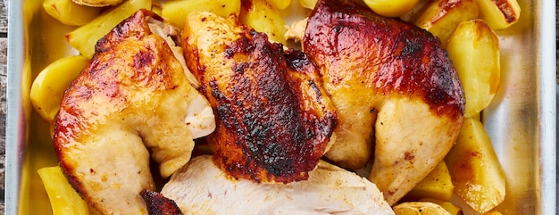Long banner with grilled chicken meat, leg, thigh with baked potatoes, garlic. top view, close up