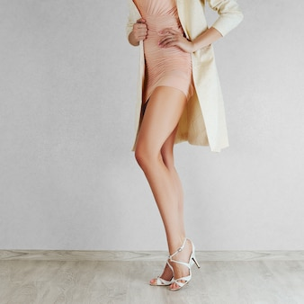 Long bare woman legs in high heel beige sandals