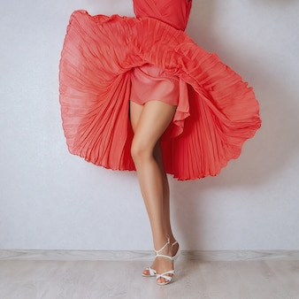 Long bare woman legs in high heel white sandals. flying dress lifted by the wind.