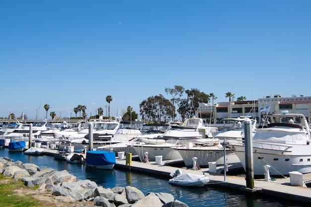 Лонг-бич, калифорния, сша - 26 марта 2021 года: гавань для лодок и парусников. лодки и роскошные яхты, припаркованные в доках частного яхт-клуба. пристань для яхт в лонг-бич, калифорния. популярное туристическое направление.