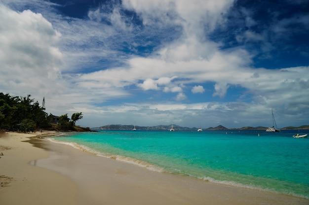 Длинный пляж с яхтой, плавающей в чистых водах карибского моря.