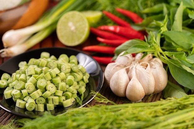 긴 콩, 마늘, 고추, 라임, 파, 차옴을 나무 테이블 위에 올려 놓습니다.