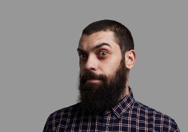 긴 수염과 눈썹을 올린 큰 콧수염 얼굴. 잔인하고 심각한 남자 총에 고립 된 중립 회색 배경.