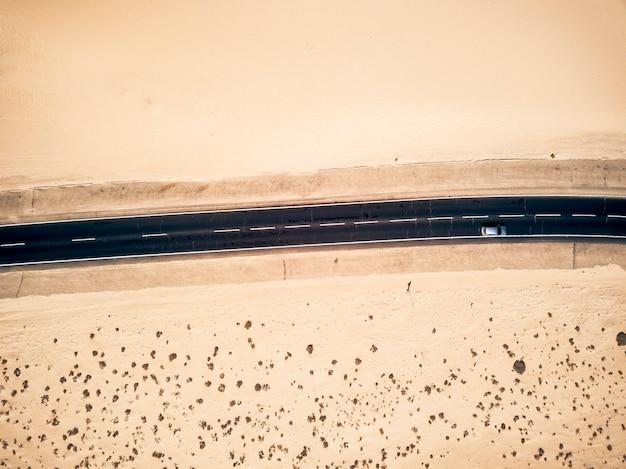 自然と屋外の周りの砂漠の真ん中にある長い黒いアスファルト道路-代替の美しい景色の良い場所での旅行と冒険の概念-空中写真