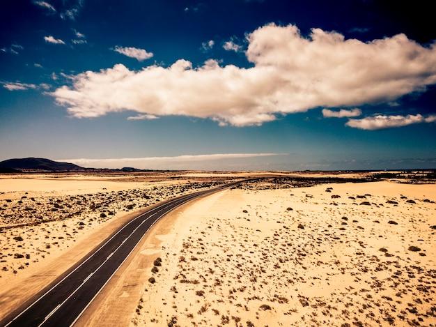 自然と屋外の周りの砂漠の真ん中にある長い黒いアスファルト道路-代替の美しい風光明媚な場所での旅行と冒険の概念-空中写真