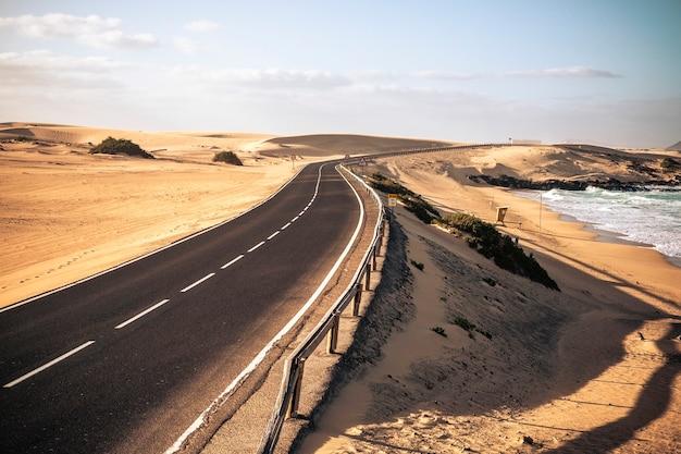 砂漠とビーチのある長い黒いアスファルト道路
