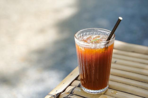 自然の背景にライチと混ぜたロングブラックコーヒー。リラックスした一日のための夏の飲み物のアイスドリンクメニュー。