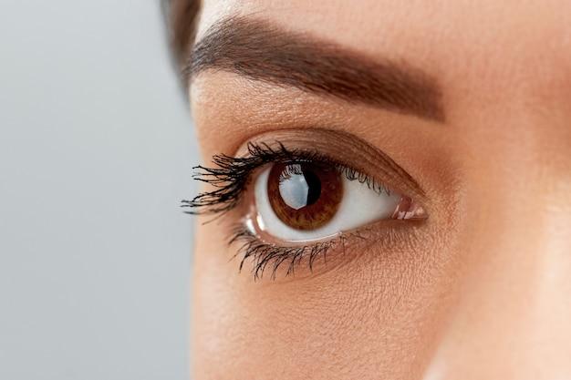 긴 검은 속눈썹. 아름 다운 여성의 눈썹과 가짜 속눈썹을 가진 큰 눈의 근접 촬영. 부드럽고 매끄러운 건강한 피부와 매력적인 전문 얼굴 메이크업을 가진 여자.